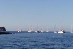Yachten hängen an den Bojen bei  Punta della Lena. Im Hintergrund Strombolicchio